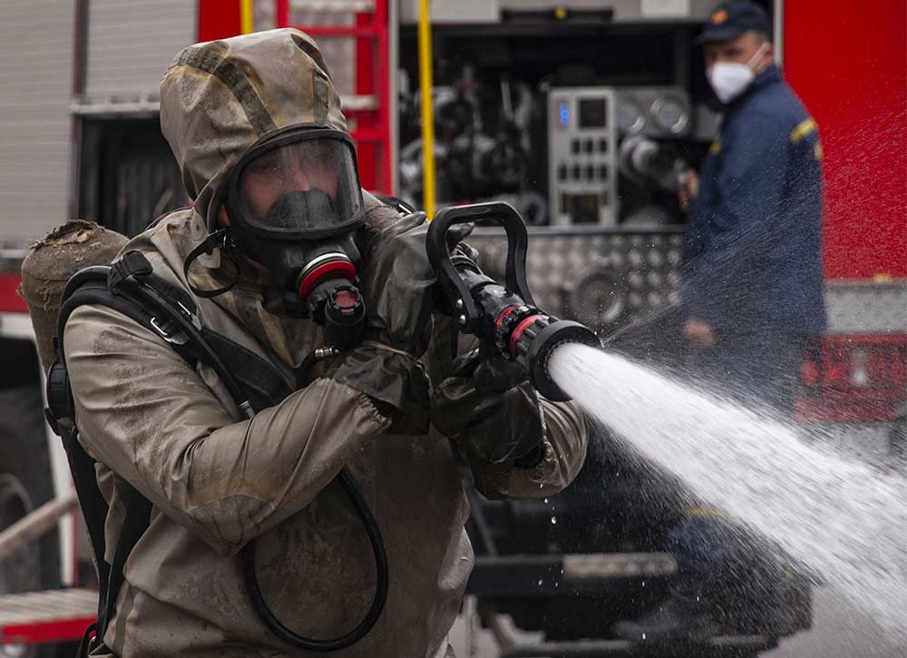 Military Fireman cleaning with a hose
