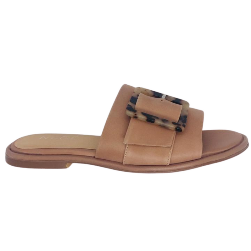 Flat summer slide in natural leather featuring a wide strap across the foot and a gorgeous tortoise shell buckle.