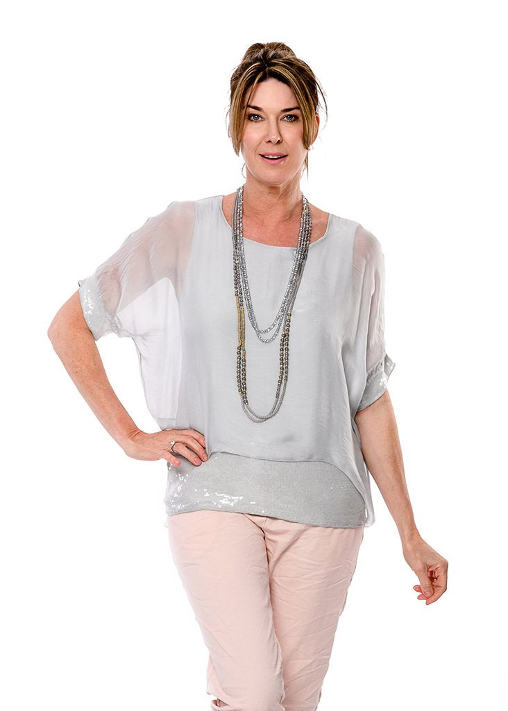 100% silk outer and soft cotton knit lining. Round neck and elbow length sleeves with a band of sequins at the hem of the sleeve and a wide band of sequins at the bottom. Flattering on most body shapes. Colour perle grey.