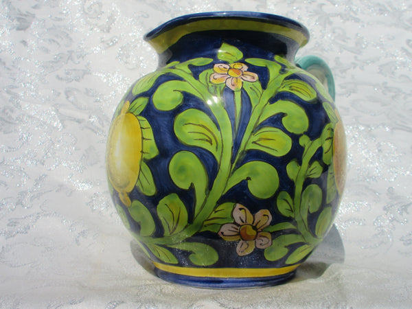 Tuscan hand made round pitcher in traditional disegn, lemons on blue background