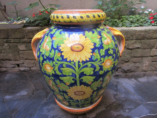 Large tuscan urns in traditional yellow lemons on blue background