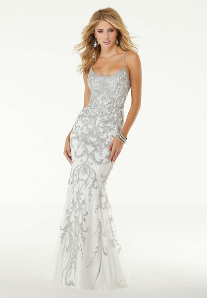 "Sparkling, scrolled appliqués lavishly cross this romantic, metallic lace Morilee 45054 gown in a statuesque silhouette that shows off Prom 2020 curves in White/Silver or Black/Gold. A strapped, scoop neckline and remarkable, beaded strappy back screams ""look at me"" to flaunt your best assets. Prom Dresses 2020"