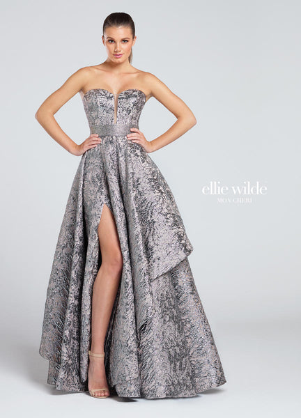 Strapless metallic jacquard A-line gown, deep plunging sweetheart neckline with illusion modesty panel, jeweled waistband, asymmetrically draped skirt with thigh-high side slit. Removable straps included.   Ellie Wilde by Mon Cheri