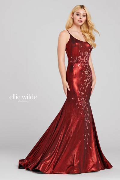 Sleeveless liquid lame fit and flare gown with a scoop neck, natural waist, sheer criss cross cut out back, stone accents throughout gown, horsehair hem and a sweep train.  Prom 2020