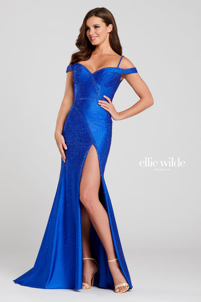 Off-the-shoulder novelty stretch fit and flare gown with a sweetheart neckline, natural waist, lace up back, stone accents throughout, high thigh slit and a sweep train.  Prom 2020