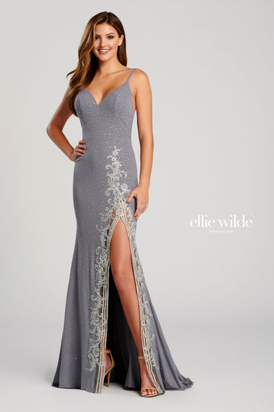 Sleeveless shimmer jersey sheath gown with a v-neck, natural waist, strappy back, stone accents throughout gown, high thigh slit with a metallic lace applique detail and a sweep train.  Prom 2020