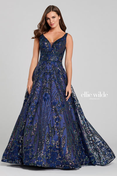 Sleeveless embroidered sequin lace a-line gown with a v-neck, double beaded waist band at the empire and the natural waist, sheer insets on the sides, v-back with an illusion detail, flowy skirt and a sweep train. Features pockets.  Prom 2020