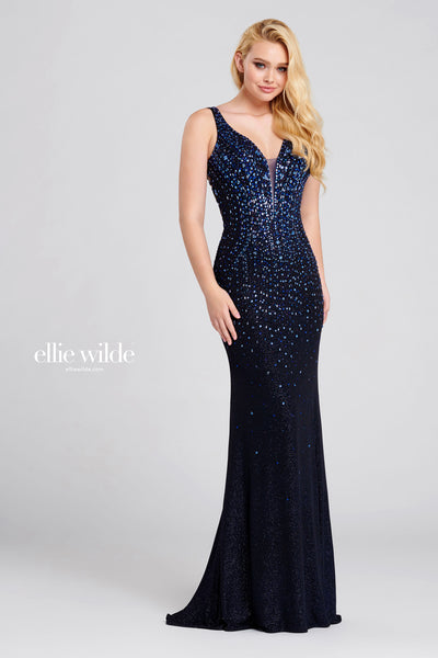 Sleeveless shimmer jersey sheath gown with a plunging v-neck, natural waist, strappy criss cross back, stone accents throughout gown and a sweep train.  Prom 2020