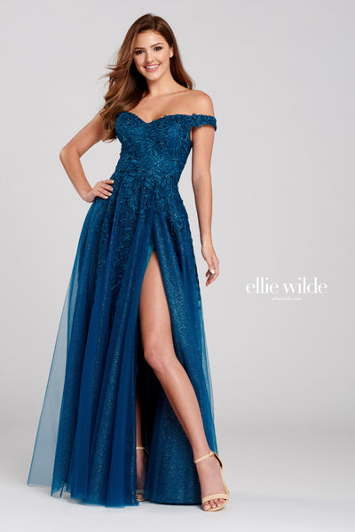 Off-the-shoulder glitter and embroidered tulle a-line gown with a sweetheart neckline, natural waist, high back, stone accents throughout gown, flowy skirt and a thigh slit.  Prom 2020
