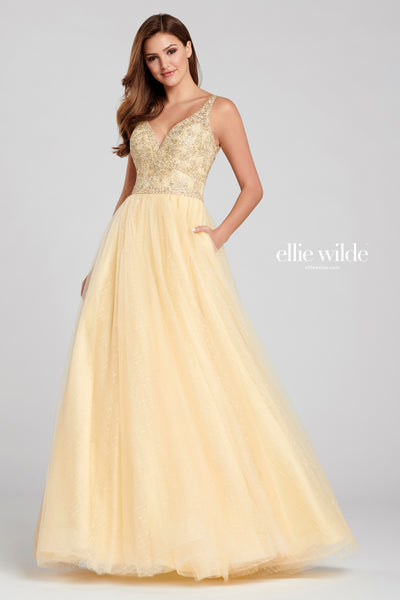 Sleeveless glitter tulle a-line gown with a v-neck, embroidered lace bodice, natural waist, lace up back and a flowy skirt. Features pockets.  Prom 2020