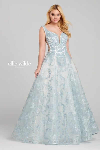 Sleeveless tulle and lace applique a-line gown with a plunging v-neck, sheer side insets, drop waist, lace up back, stone accents throughout gown and a horsehair hem. Features pockets.  Prom 2020