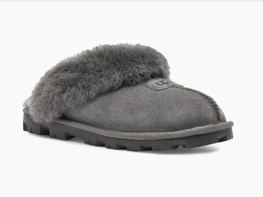 Coquette - The Classic Ugg Slipper in Grey. Nothing feels cozier than this Ugg classic slipper mule. Perfect for when you are working from home or walking the dog. Suede sheepskin upper & sock lining, lightweight full rubber sole.