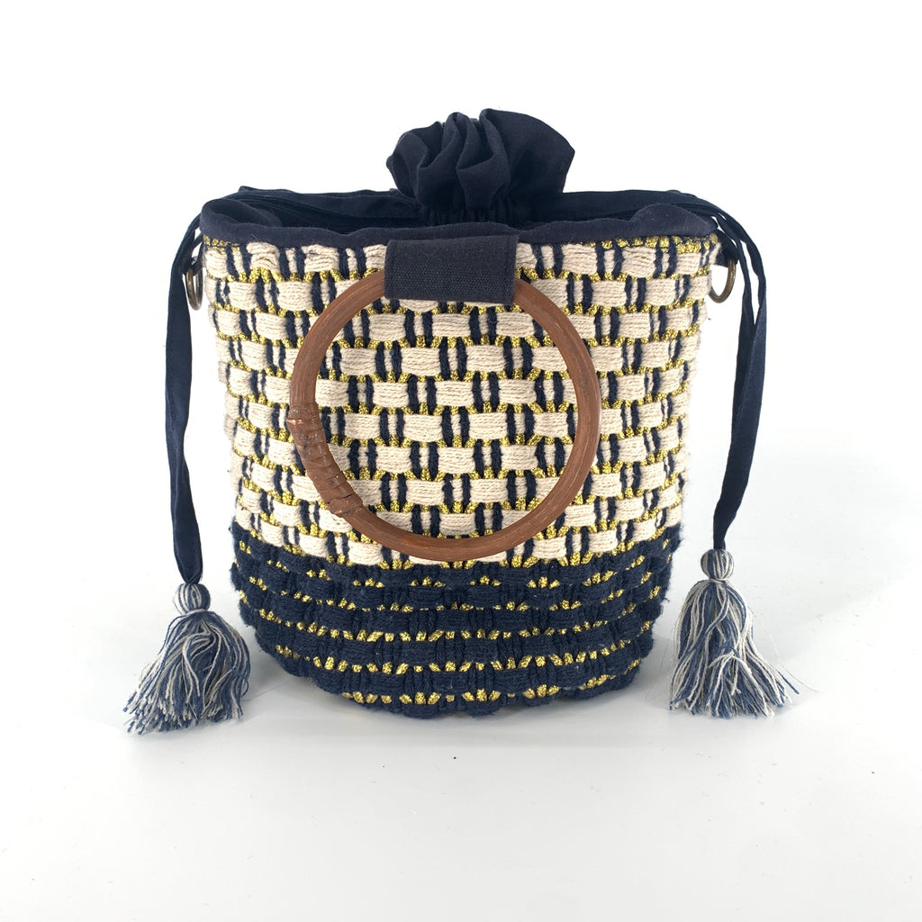 America and  Beyond ABR19024 - The Woven Bucket Crossbody. This versatile handbag has ratan handles and the option to remove the crossbody strap. Pull string closure with an interior zipper pouch. Eco-conscious materials.