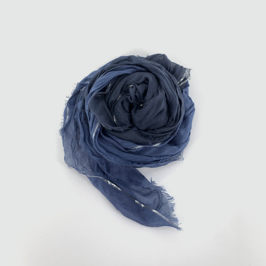 "Blue Pacific CGL3256 - Solid Tissue Scarf in Denim with Metallic Trim by Blue Pacific. Super silky and lightweight makes this the perfect, hand dyed, layering piece. Lovely metallic detailing runs along the fringed edges. Oversized at 56"" x 56"" it can also be used as a wrap. Made in Spain."