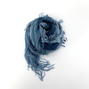 "TSD3256 - Solid Tissue Scarf in Ombre Blue Denim by Blue Pacific. Super silky and lightweight makes this fringed scarf the perfect, hand dyed, layering piece. Oversized at 60"" x 60"" it can also be used as a wrap. Made in Spain."