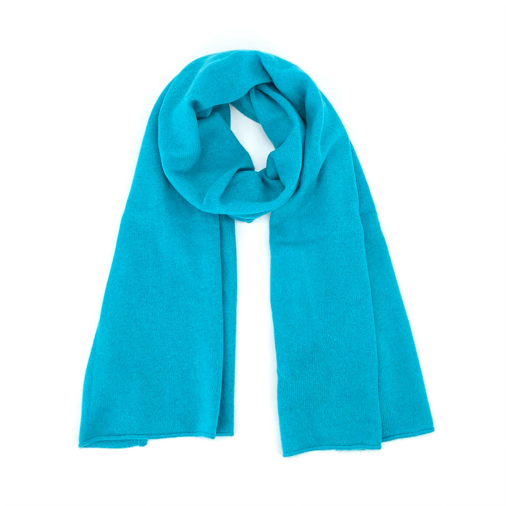 Brodie The Cashmere Scarf in Turquoise Soft to the touch and a great layering piece. Makes the perfect holiday gift. Available in Blue, Charcoal, Neon Orange, Neon Pink, Tan, and Turquoise.