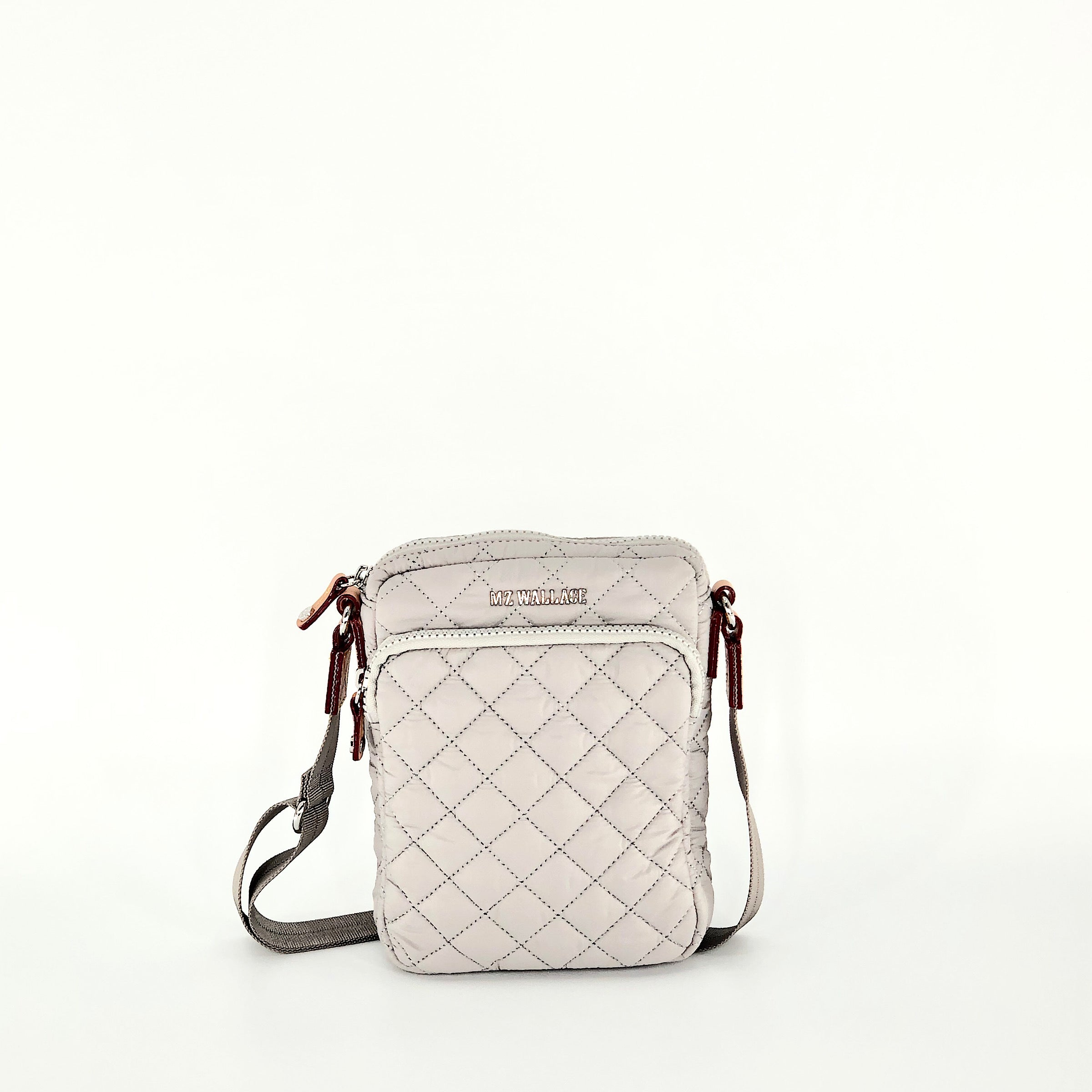The Metro Crossbody - Fog by MZ Wallace. The Metro Crossbody is an update allowing for more room to truly be hands-free. Adjustable strap and 2 external pocket allows for all your essentials and easy access to be active you. Zip top closure.