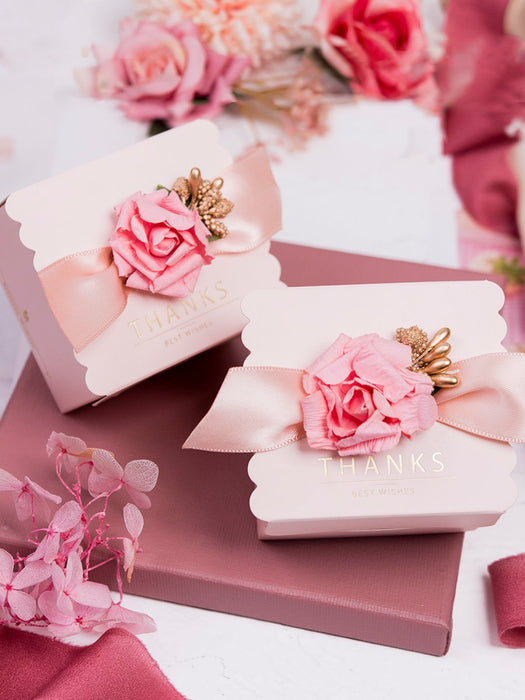 Light pink wedding with ribbon bow and tag. Elegant personalized wedding candy box for guests sweets