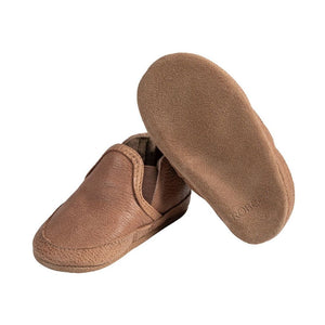 Left shoe shows simple brown soft kids easy on shoes with elastic side panels, with right shoe tilted up to show soft brown bottoms
