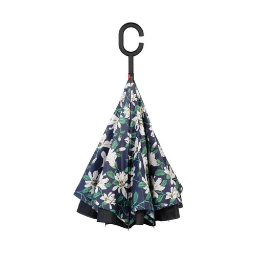 Closed Knirps reversible umbrella has c-shaped handle and white flower pattern on navy with green leaf design
