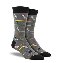 Load image into Gallery viewer, A pair of grey crew socks with hockey sticks on them.