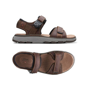 Dark tan Untrek sandal by Clarks side view shows 2 straps over foot and one around ankle with thick grey outsole and the top view shows tan footbed