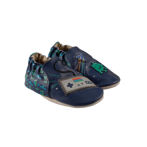 Dark blue kids easy on shoes with retro game controller on right foots toefoot and pixel alien and space ship on left foots toe