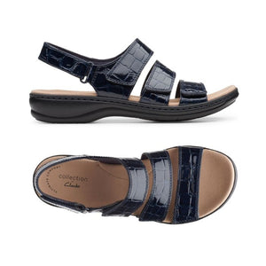 A Black crocodile texture leather Melinda sandal by Clarks from a side and top view of 3 wide over the foot straps and a velcro back strap with a small platform heel