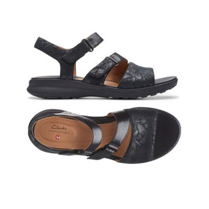 The Ease sandal by Clarks has Velcros on the side of 2 straps and a tan footbed with floral black metallic pattern.