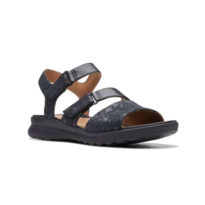 An Ease sandal by Clarks that has a black metallic patterned sandal with a thick strap over toe, thin Velcro strap across foot and around ankle.