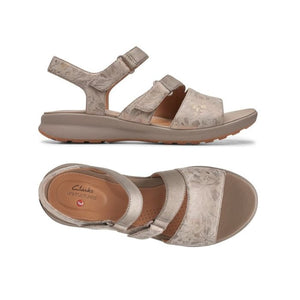 The Ease sandal by Clarks has Velcros on the side of 2 straps and a tan footbed with floral taupe metallic pattern.