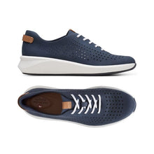 Load image into Gallery viewer, The top view of the Rio Tie sneaker by Clarks shows the white laces and dotted line perforations across the toe and tan footbed while the side view shows the perforations wrap around and the white thick outsole