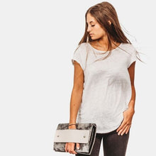 Load image into Gallery viewer, Brown haired young girl holding denim JTB Bold clutch in hand in white t-shirt and black jeans
