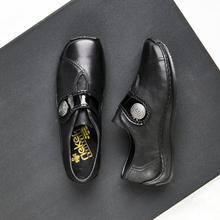 Load image into Gallery viewer, Tpo and side of Black slip on shoe with oversize across foot flap with circle design closure on a black square floor