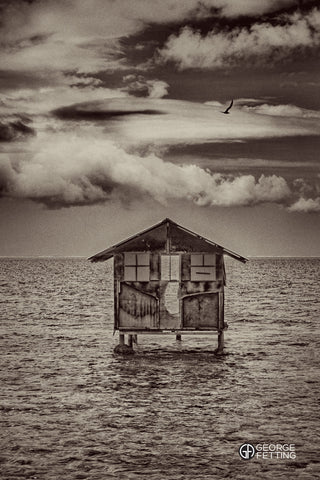 Slightly surreal view of the remnants of a fisherman's hut sits over the water