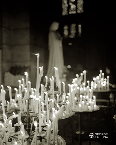 A whisp of breeze caresses a candle within the Basilica Sacre Couer