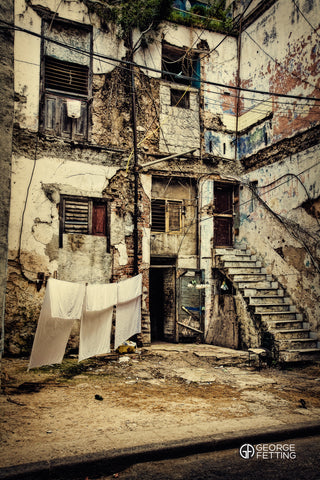 three white sheets hanging to dry outside derelict building