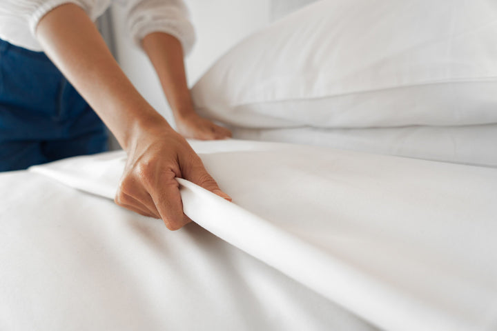 Woman making bed with white bed sheets