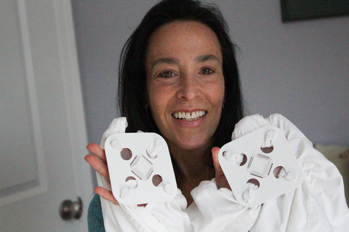 Woman holding two Wad-Free™ for Bed Sheets attached to a flat sheet and a fitted sheet to prevent laundry wads