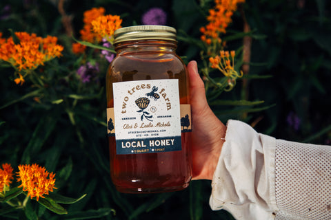 Leslie holding a jar of Two Trees honey, featuring a Local Press & Design custom label.