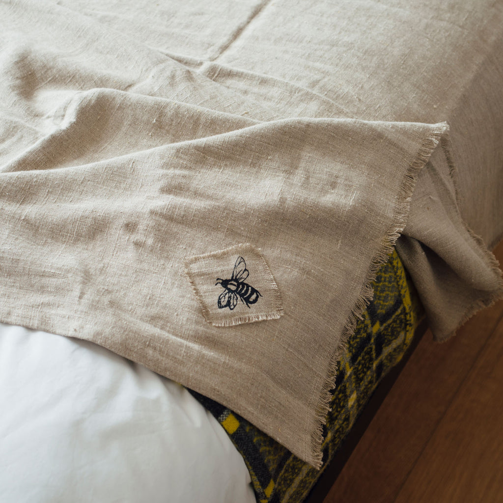 honey bee linen throw in natural linen on the bed