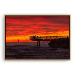 Couple watch sunset from the end of jetty in North Beach, Western Australia framed canvas in raw oak