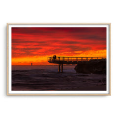 Couple watch sunset from the end of jetty in North Beach, Western Australia framed in raw oak