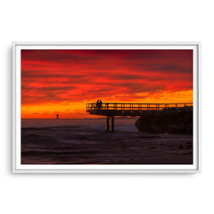 Couple watch sunset from the end of jetty in North Beach, Western Australia framed in white