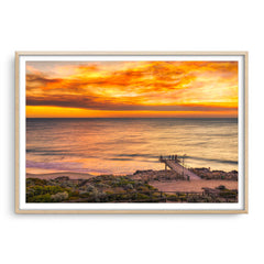 Smoke filled sunset over North Beach Jetty in Perth, Western Australia framed in raw oak