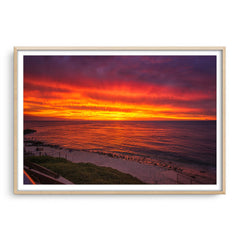Fiery skies over Mettams Pool in Perth, Western Australia framed in raw oak