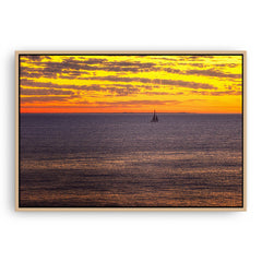 Boat sailing past rottnest island at sunset in Perth, Western Australia framed canvas in raw oak