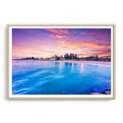 Blue waters and magenta skies over Cottesloe in Perth, Western Australia framed in raw oak
