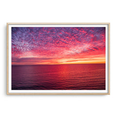Sunset over the ocean at Mettams Pool in Perth, Western Australia framed in raw oak