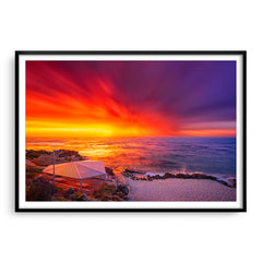 An explosive sunset over Mettams Pool in Perth, Western Australia framed in black